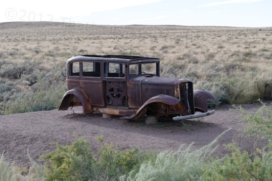 An early Ford perched on cinder blocks commemorates the location of the highway.