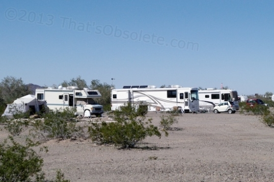 Three motorhomes. Tents and canopies offer some relief from cabin fever. Smaller units lean toward tents, while canopies are popular even with the largest motorhomes.
