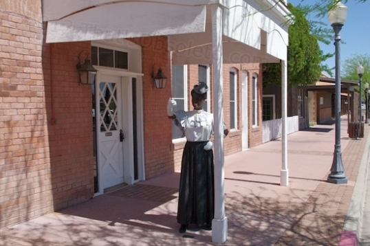 I wondered about this until I looked it up. This is a depiction of Elizabeth Smith, who originally began the Vernetta Hotel in 1905, which catered to railroad passengers and primordial tourists to Castle Hot Springs and Wickenburg. She came from out East, and had James Creighton design and build it. It's now offices for Remuda Ranch and is called the Hassayampa Building.