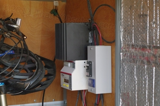 Here's the less glamorous part. Mike mounted the solar controller and a circuit breaker box on the bulkhead between the driver's seat and the cargo area, next to the hinged door that allows entry. That bulkhead protects the driver from flying cargo in case of an accident. Mike wound up selecting the same big controller that I have, except he added a digital readout that allows reprogramming and monitoring lots of confusing data. The weird-looking thing on the left is a bike helmet - he's somehow stuffed a bicycle in there, too!
