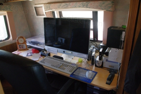 The Command Center. A scratch-built floor-to-ceiling reference bookshelf is directly in back of the chair. Book toppling during transport is prevented by thin wire cables that are easily hooked into place across each shelf. The iMac is screwed down to the work surface and so far, nothing else wants to move.