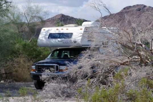 A standard truck camper may have height clearance issues now and then, but can tuck into the bushes for privacy. Narrow trails and low trees are not its friends.
