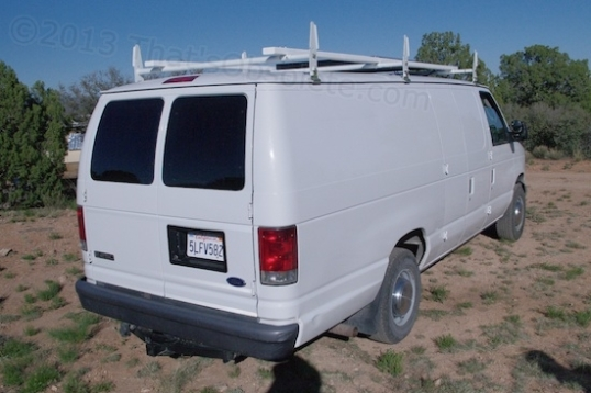 This nice cargo van came with rear windows, and it has a large solar panel installed on a roof rack.