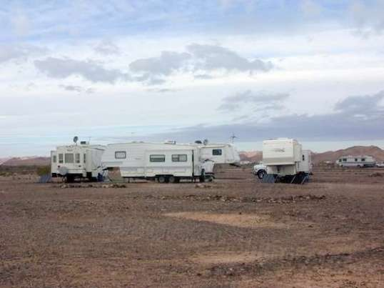 The quad of RVs next door. One has a wind generator that makes sounds like a thousand grasshoppers flying. A couple of others use ground-based solar panels anchored with big rocks and fuel cans.