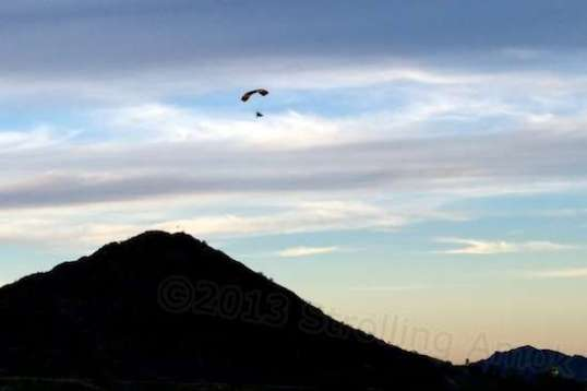 One of two engine-powered hang gliders lazily makes for home at sunset.