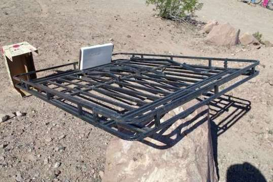 The Jeep's self-supporting roof rack, handmade by Charles to hold mucho weight, lies in the desert with a $400 for sale sign.