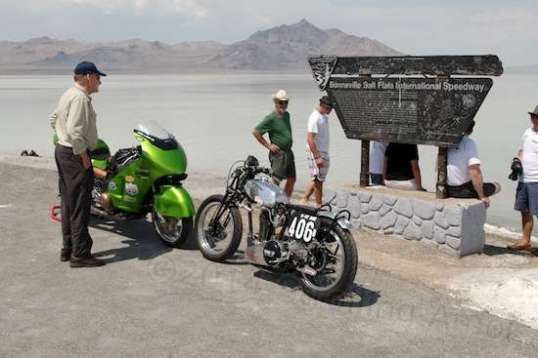 Two runners, one vintage and the other modern, are posed before the Bonneville Speedway sign in consolation.