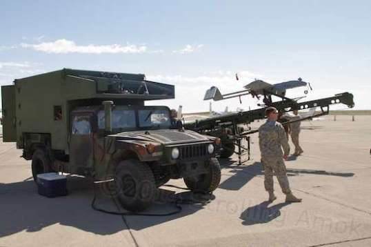 An R/C model aircraft on steroids - the military version, a drone, fitted with a camera turret. Its launcher is towed by a specially-outfitted HUMVEE.