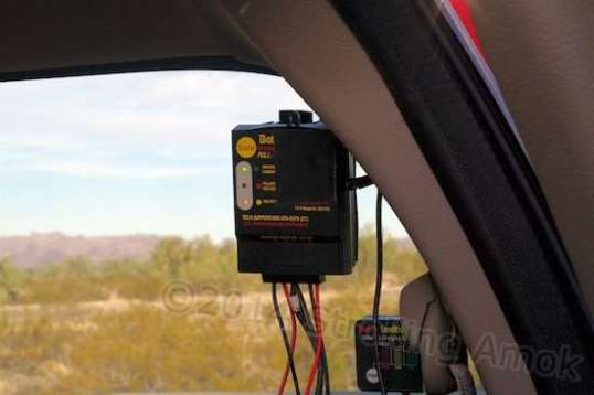 A Batteryminder SCC-180 solar controller is attached to the truck's rear window with adhesive-backed Velcro. The little box below is Batteryminder's version of a voltage meter.