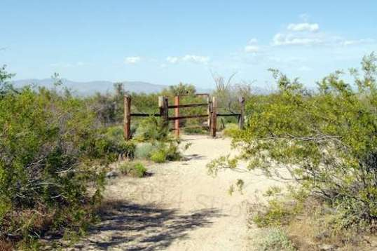 A gate at a bend in the trail, possibly at private property. In any case, the reddish pole on the far side keeps ATVs from wandering in.