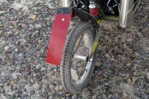 Hillbilly, anyone? This idiocy kept the salt from flinging forward into the basket. The red plastic was cut from the bottom of a kitchen sink tray. Held by the screw holing the reflector, it worked well until bumps bounced the end into the tire and wrapped it forward. If I go again next year, I'll trim its length.