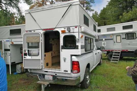 This is called a truck camper, made by Four Wheel. Sparse in features, lightweight and built to survive off-road pounding and bed flex, it's been continually honed since the 70s.