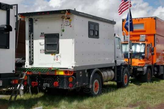A camper body on a flatbed Unimog, with storage boxes underneath.