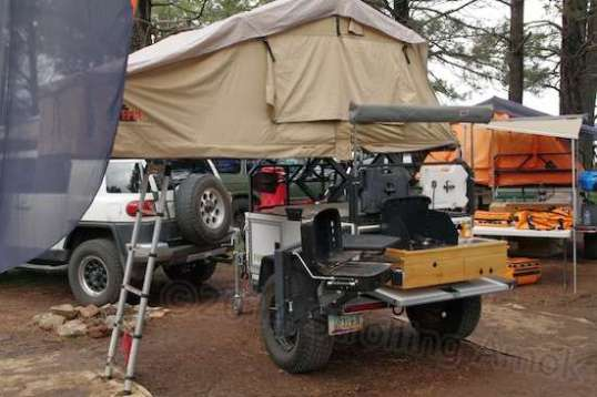 The rear of the same rig offers an awning over a counter, stove, grill, and sink. And it can handle rougher ground than the vehicle towing it.