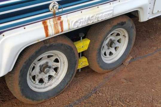 The Camco tire chock is challenged even when cranked down hard. They must be periodically re-tightened. (Those brown stains on the fender are from water at a commercial campsite in Marengo, Illinois.)
