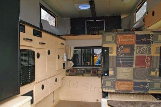 Driver's side of a Granby Side Dinette on display. Some of that cabinetry is occupied by appliances, propane bottles, and electronic controls.