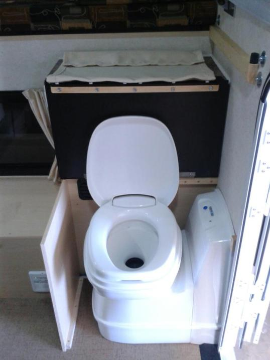Come on, I know y'all just love toilets, so here's what the cassette toilet option looks like. The bowl rotates at its base for getting it of the aisle, and is then shrouded over when not in use. Some people may wish to also close the entry door!