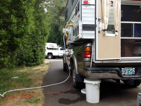In a regular RV park with hookups, you can the Four Wheel's freshwater inlet and shore power socket. The white hose at the rear is connected to the greywater outlet, and here leads to a bucket, as used in the field. A longer hose would allow for a sewer connection.