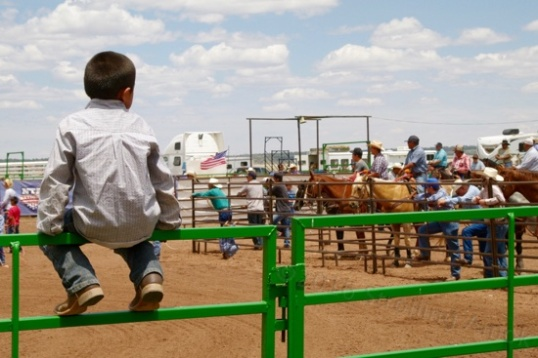 This little boy impatiently awaits the resumption of steer roping. Here, ropers don't show up, families do.