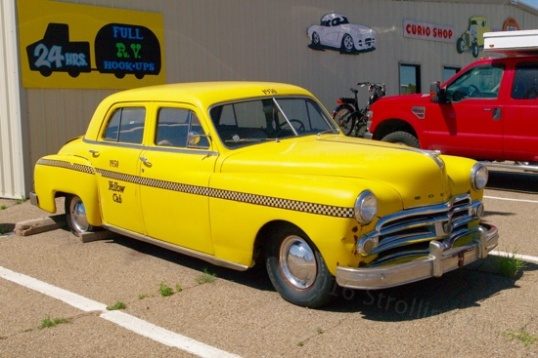 A taxi outside, though probably just a faux taxi to make a dowdy old Dodge more interesting. Hey, it works.
