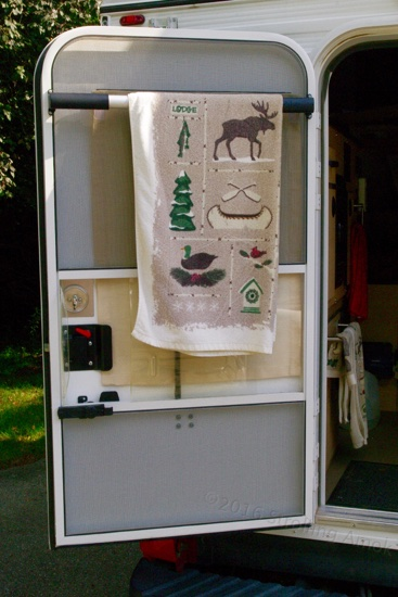 A Camco door bar doubles as a decent towel rack. I tried it with VHB tape to avoid drilling the door, but the grip surfaces are way too small. The screen door's very narrow frame makes accurate hole location important, and don't be ham-handed about torquing the screws down, either!