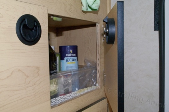 One of several cabinet bays, this one sporting a plastic tray to keep things upright and in place during off-roading hi-jinx. The door latch is positive locking, not spring tensioned rollers or friction pads.