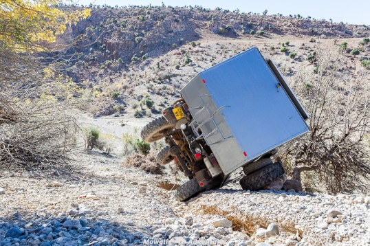 This overlanding journey has become inconvenient! Beside the rig's center of gravity, where you store things can matter, particularly with a narrow wheel track. Looking at the terrain, you have to wonder just how high the CG is to flop over like that.