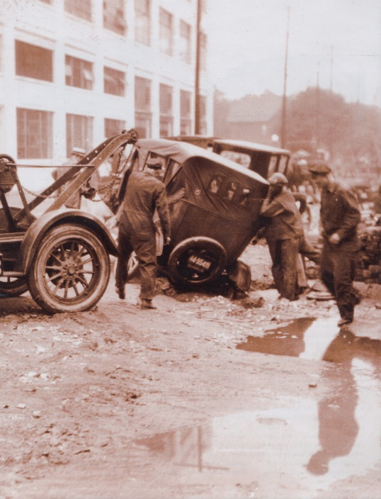 In those days, automobile clubs had bigger issues to face, given the road conditions and signage. The Flat Tire Club changed its name to the Hoosier Motor Club in 1911, and that's one of their tow trucks yanking out this car that has a wheel caught in an epic rut. ..And we think potholes are bad!